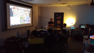 Gamers huddle around the projector with GameCube controllers getting ready for a Smash-fest!