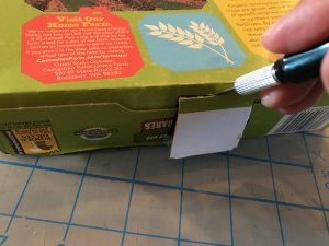 Exacto knife cutting hole in the end of a cereal box